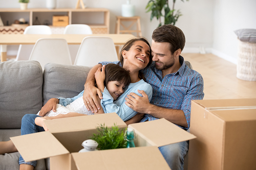 a family sitting on a couch surrounded by unpacked boxes