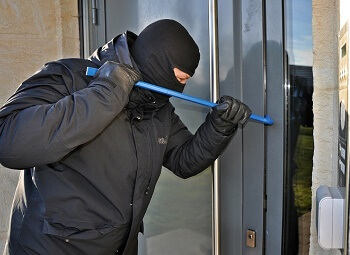 Masked burglar attempts to use a crowbar to break into a house