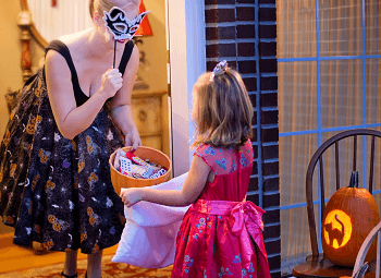 Woman wearing a mask answers the door for a litter girl trick or treater