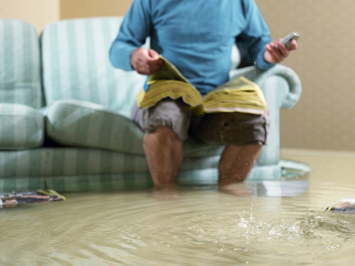 Person Sitting on Couch in Flooded Living Room